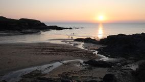 Sunset at the beach Treyarnon Bay Cornwall England UK with people in the sea summer evening stock video footage