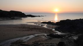 Sunset at the beach Treyarnon Bay Cornwall England UK with people in the sea summer evening stock video