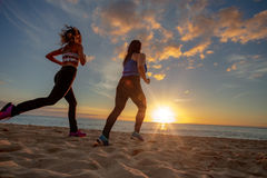 Sunset beach two fit girls jogginr on sand. Running girls jogging at beachside at sunset time. Motion blurred image Royalty Free Stock Image