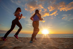 Sunset beach two fit girls jogginr on sand. Running girls jogging at beachside at sunset time. Motion blurred image Royalty Free Stock Photo