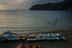 Sunset beach view with empty boats in front of the sea. Levanto, Stock Photos