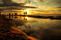 Sunset beach and walking people. Royalty Free Stock Photo