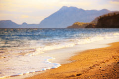 Sunset beach. It is a warm mysterious sea shore, which is calling for you to quickly go on a journey Stock Photo