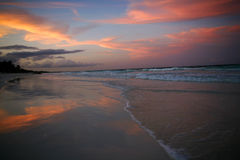 Sunset on beach. Sunset on a beach with water reflecting the sky Royalty Free Stock Images