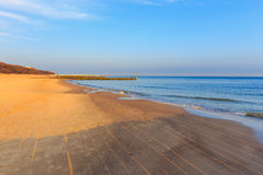 Sunset on the beach with a wooden breakwater Royalty Free Stock Photography