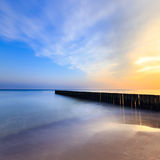 Sunset on the beach with a wooden breakwater Royalty Free Stock Photo