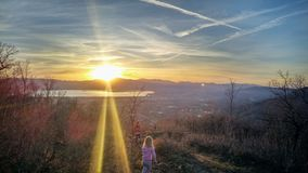 Two Kids Looking Across Valley at Sunset. A sunset beaming across the valley at the golden minute while two kids walk to the edge of the mountain bench Royalty Free Stock Photo