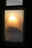 Sunset beams through the frozen glass window. View of frozen glass window with sunset background royalty free stock photography
