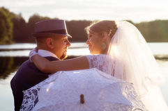 Sunset, beautiful bride with the groom on the background of wate Stock Image