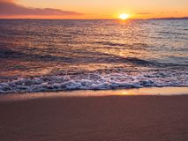 Sunset on a beautiful empty sandy beach - foamy waves stock photography