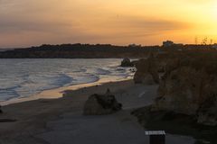 Sunset on the beautiful sandy beach with huge rocks. In Portugal Stock Image