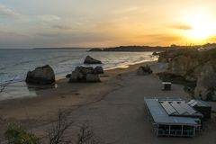 Sunset on the beautiful sandy beach with huge rocks. In Portugal Royalty Free Stock Photos