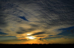 Sunset.  Beautiful sky. Sunset. Yellow rays on a blue sky, white clouds Royalty Free Stock Photography