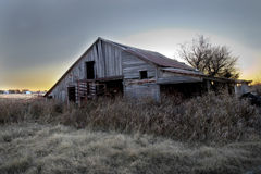 Sunset Behind an Abandoned Barn. The setting sun pulls the crumbling and falling barn with it as it continues to set below the horizon Royalty Free Stock Photos