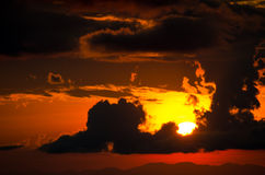 Sunset. Behind black cloud with orange sky Stock Photo