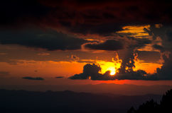 Sunset. Behind black cloud with orange sky Royalty Free Stock Photography