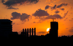 Sunset behind a building under construction. Royalty Free Stock Photo