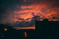 Sunset behind buildings with red light royalty free stock photography