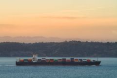 Sunset behind a Cargo Freighter Ship for International Import and Export of Goods Stock Photography