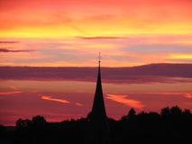 Sunset behind church tower royalty free stock photography
