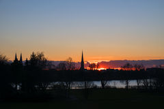 Sunset behind the church towers of Luebeck, northern Germany, pa Stock Photos