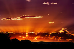 Sunset behind clouds stock image