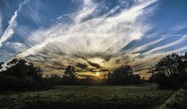 Sunset behind clouds in blue skies. Sunset behind white clouds in blue skies with silhouette of trees in countryside stock photos