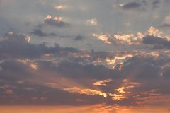 Sunset behind the clouds royalty free stock image