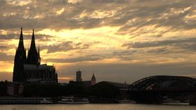 Sunset behind Cologne Cathedral and trains on Hohenzollern Bridge above the River Rhine, Germany. COLOGNE CATHEDRAL, COLOGNE, GERMANY - JULY 31 2017: 4K video stock video footage