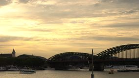 Sunset behind Cologne Cathedral, trains on Hohenzollern Bridge and tanker ship sailing on the River Rhine, Germany. Cologne Cathedral, Cologne, Germany - July 31 stock video footage