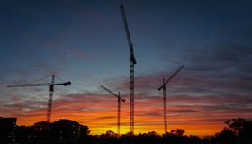 Sunset behind cranes transforms building site royalty free stock photos