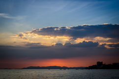 Sunset behind dark cloud above island Royalty Free Stock Photography