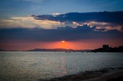 Sunset behind dark cloud above island Stock Photo