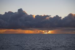 Sunset behind dark clouds over Ocean Royalty Free Stock Photography