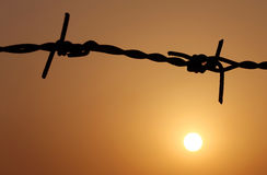 Sunset behind a fence of barbed wire Royalty Free Stock Photos