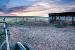 Sunset behind fencing and barn in Eastern Plains Colorado Royalty Free Stock Photo
