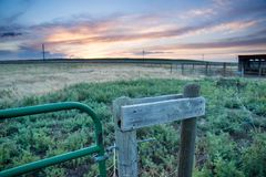 Sunset behind fencing and barn in Eastern Plains Colorado Royalty Free Stock Photography