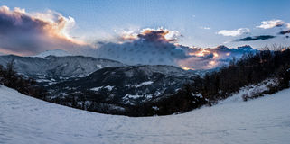 Sunset behind the frozen mountains, with snow and clouds royalty free stock image