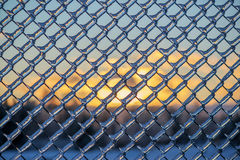 Sunset Behind an Ice Covered Chain Link Fence Royalty Free Stock Photos