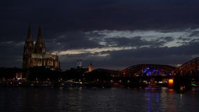Sunset behind illuminated Cologne Cathedral and The Hohenzollern Bridge over the River Rhine, Germany. 4K video clip of sunset behind illuminated Cologne stock footage