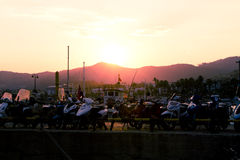 Sunset behind motorcycles. The sun is setting in the background behind a row of motorcycles Royalty Free Stock Photography