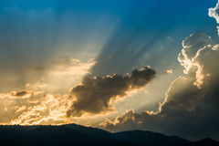 Sunset behind mountain with beautiful sunbeam through the cloud Stock Photo