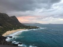 Sunset behind the mountain, Hawaii. Sunset over the blue waters of Hawaii.  The clouds are rolling in and the sun is setting behind the mountain.  You can see Stock Image