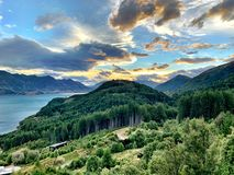 Sunset behind the mountains in Queenstown, New Zealand. A beautiful sunset behind the mountains in Queenstown with green forest like trees framing the lake and stock images