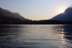 Sunset behind mountains surrounding a flat surface lake Stock Photography