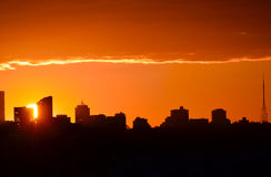 Sunset behind North Sydney. Glowing orange sun setting behind city buildings in silhouette (North Sydney, Australia Stock Photo