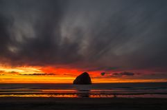 Sunset behind Rock under dark clouds in Cape Kiwanda royalty free stock photos