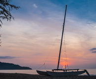 Sunset behind saiboat. On the beach Stock Photography