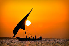 Sunset behind sailboat. On ocean silhouette Stock Photos