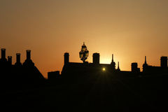 Sunset behind silhouetted roofs, London, England. A postcard with the sun setting behind roofs and peaks in London, nearby The Big Ben, and The Westminster Royalty Free Stock Images